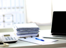 Un carnet, ordinateur portable, stylo, document sur papier de graphique sur la table de bureau derrière les abat-jour blancs Photos stock
