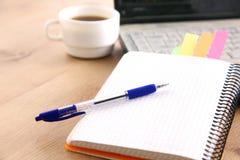 Un carnet, ordinateur portable, stylo, document sur papier de graphique sur la table de bureau derrière les abat-jour blancs Image libre de droits