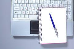 Un carnet, ordinateur portable, stylo, document sur papier de graphique sur la table de bureau derrière les abat-jour blancs Photographie stock libre de droits