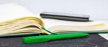 Un carnet ouvert avec le stylo et téléphone pour enregistrer important dedans images stock