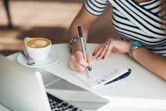 Un carnet vide blanc avec un stylo de luxe et une tasse de café de Latte avec l'ordinateur portable brouillé à l'arrière-plan Photographie stock