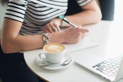 Un carnet vide blanc avec un stylo de luxe et une tasse de café de Latte avec l'ordinateur portable brouillé à l'arrière-plan Image stock