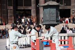 Un carpentiere di tre giapponesi è costruzione la fase, facendo uso di un colpo di legno del martello alle componenti della fase immagine stock libera da diritti