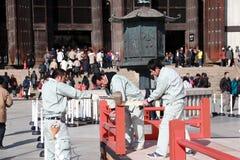 Un carpentiere di tre giapponesi è costruzione la fase, facendo uso di un colpo di legno del martello alle componenti della fase fotografia stock libera da diritti