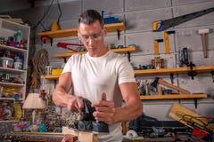 Un carpentiere lavora alla falegnameria la macchina utensile Sega i dettagli della mobilia con una sega circolare Processo di seg immagini stock