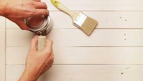Un carpentiere prepara il suo posto di lavoro: apra una latta con pittura blu video d archivio