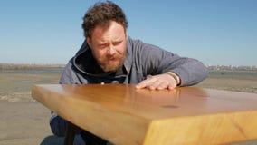 Un carpintero de ojos azules con una barba y un bigote contra un cielo azul toca la superficie de la tabla, hecha por él a mano metrajes