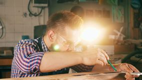 Un carpintero dibuja una línea en la madera con un lápiz almacen de video