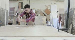 Un carpintero joven que da vuelta al tornillo penetrante con un destornillador en una producción de los muebles almacen de metraje de vídeo
