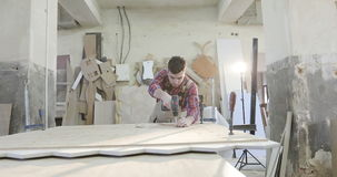 Un carpintero joven trabaja en una fábrica de carpintería almacen de metraje de vídeo