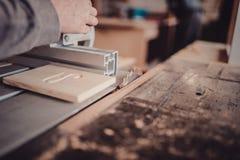 Un carpintero trabaja en carpintería la máquina-herramienta Asierra los detalles de los muebles con una sierra circular Foto de archivo