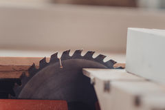 Un carpintero trabaja en carpintería la máquina-herramienta Asierra los detalles de los muebles con una sierra circular Imagen de archivo libre de regalías