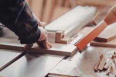 Un carpintero trabaja en carpintería la máquina-herramienta Carpintero que trabaja en las máquinas de la carpintería en tienda de Imagen de archivo
