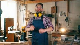 Un carpintero trabaja en una carpintería, sonriendo en la cámara almacen de video