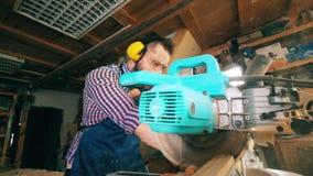 Un carpintero utiliza vio el banco mientras que trabaja con madera metrajes