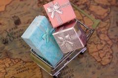 Un carrello con i contenitori di regalo sulla mappa di mondo consegna Fotografie Stock Libere da Diritti