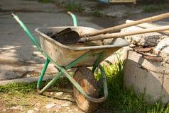 Un carrello con le pale ed i rastrelli nel parco immagine stock libera da diritti