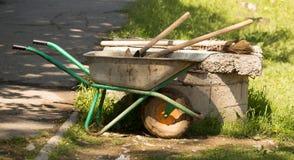 Un carrello con le pale ed i rastrelli nel parco fotografia stock