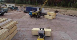 Un carrello elevatore porta un fascio di legno, un carrello elevatore con i giri di un carico attraverso la fabbrica video d archivio