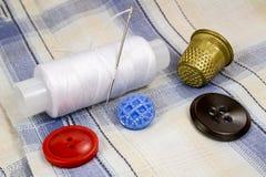 Un carrete del hilo blanco con una aguja, botones coloreados y un dedal en el fondo de la camisa Imagenes de archivo