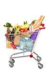 Un carro de compras por completo con las tiendas de comestibles Imágenes de archivo libres de regalías