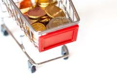 Un carro de la compra con las monedas euro Imagen de archivo