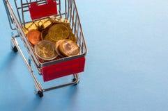Un carro de la compra con las monedas euro Foto de archivo libre de regalías