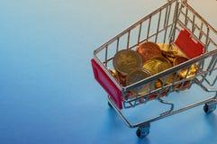 Un carro de la compra con las monedas euro Imagen de archivo libre de regalías