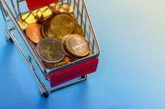 Un carro de la compra con las monedas euro Fotografía de archivo
