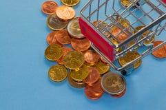 Un carro de la compra con las monedas euro Foto de archivo