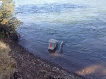 Un carro de la compra mojado solo en el río foto de archivo