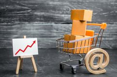 Un carro del supermercado cargado con las porciones de cajas y de una flecha ascendente roja Ventas y comercio electrónico en lín fotografía de archivo libre de regalías