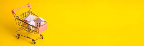 Un carro del supermercado con las casas de madera se coloca en un fondo amarillo El concepto de compras caseras y de márketing, c imagen de archivo