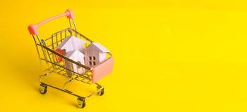 Un carro del supermercado con las casas de madera se coloca en un fondo amarillo El concepto de compras y márketing casero, comer Fotografía de archivo libre de regalías