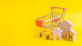 Un carro del supermercado y una casa en un fondo amarillo Comprando y vendiendo de las propiedades inmobiliarias, construcción Ap Fotografía de archivo