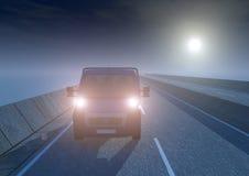 Un carro en la carretera en el medio de la noche Foto de archivo libre de regalías