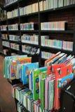 Un carro y estantes con los libros en diversos colores en la biblioteca Imagen de archivo