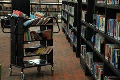 Un carro y estantes con los libros en diversos colores en la biblioteca Imágenes de archivo libres de regalías