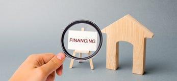 Un cartel con el financiamiento de la palabra y una casa de madera Atracción de la inversión en la vivienda y edificios arquitect fotos de archivo libres de regalías