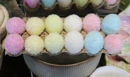 Un carton d'oeufs de pâques décoratifs brouillés scintillants en pastel Images stock