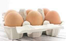Un cartone di sei uova organiche marroni del pollo Fotografia Stock