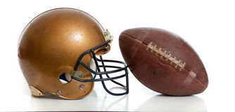 Un casco de fútbol americano y un fútbol retros del oro en un fondo blanco Fotos de archivo libres de regalías