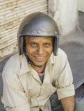 Un casco que lleva sonriente del hombre de la vespa fotos de archivo