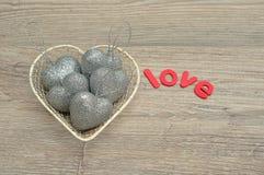 Un casier métallique a rempli de babioles argentées de forme de coeur et d'amour de mot Photographie stock libre de droits