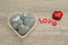 Un casier métallique a rempli de babioles argentées de forme de coeur et l'amour de mot et une babiole rouge Image libre de droits