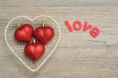 Un casier métallique a rempli de babioles rouges de forme de coeur et d'amour de mot Images libres de droits