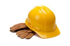 Un casque antichoc et un cuir jaunes fonctionnent des gants sur le blanc Images stock
