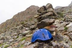 Un casque protecteur de grimpeurs sur la roche les casques un bleus sur le bâti photos stock