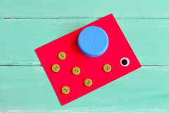 Un casquillo de una botella plástica, botones, hoja de la cartulina, un ojo plástico Fotografía de archivo libre de regalías