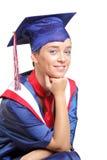 Un casquillo y un vestido que desgastan felices del estudiante de graduación Imagen de archivo libre de regalías